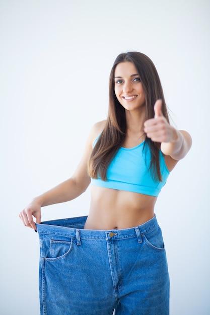 Женщина показывает ее потерю веса и носить ее старые джинсы Premium Фотографии