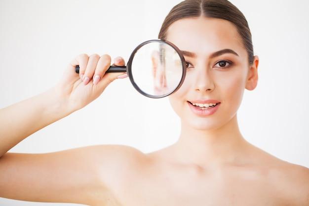 Женщина смотрит через лупу и улыбается крупным планом Premium Фотографии
