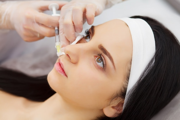 女性の唇に美容注射を行う美容師 Premium写真