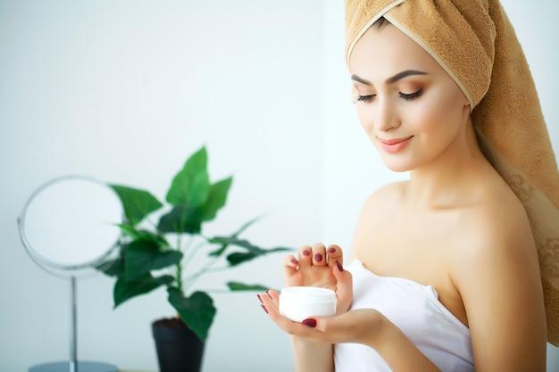 Красивая женщина, использующая средства по уходу за кожей, увлажняющий крем или лосьон и средства по уходу за кожей, заботится о ее сухой коже. увлажняющий крем в женских руках Premium Фотографии