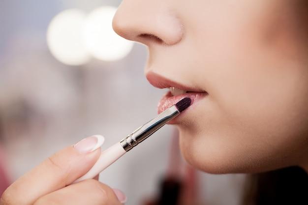 メイクアップアーティストがブラシでモデルの唇に口紅を適用します。 Premium写真
