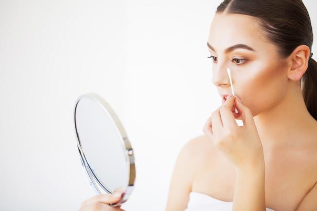スキンケア。屋内で鏡で見ている新鮮な健康的な肌とセクシーな若い女性の肖像画 Premium写真