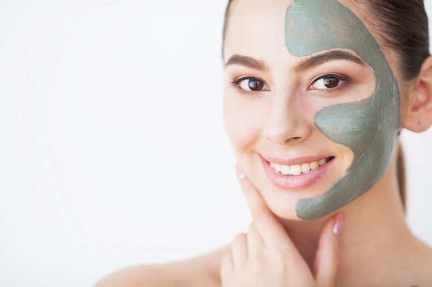Забота о коже. молодая женщина с косметической глиняной маской держит огурец в ванной Premium Фотографии