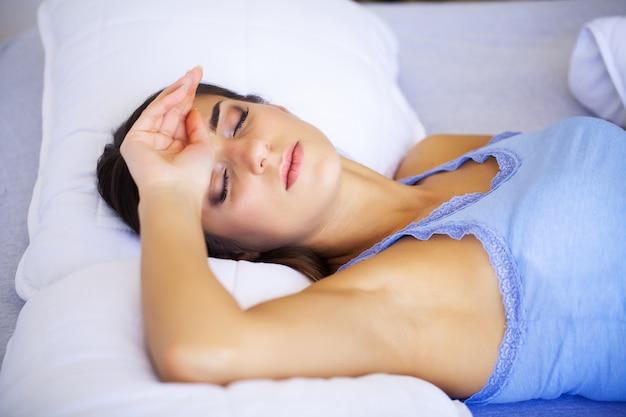 Головная боль. усталая, измученная молодая женщина, которая страдает от сильной головной боли от напряжения. портрет красивой больной девушки, страдающей от сильной мигрени, ощущения давления и стресса Premium Фотографии