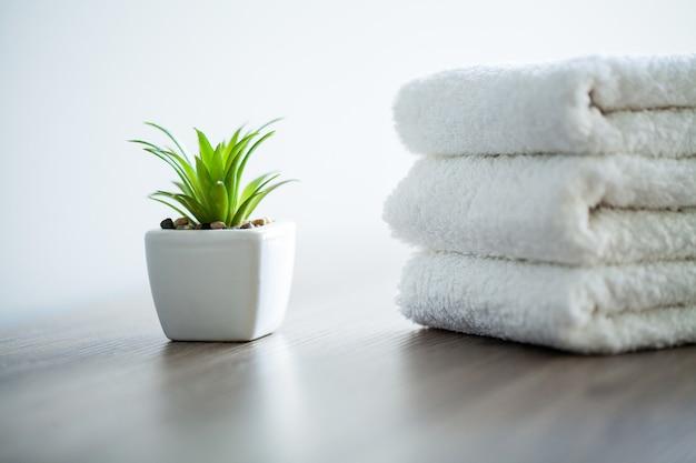 スパ。スパのバスルームで使用する白い綿のタオル。タオルのコンセプト。ホテルおよびマッサージ店の写真。純度と柔らかさ。タオルテキスタイル Premium写真