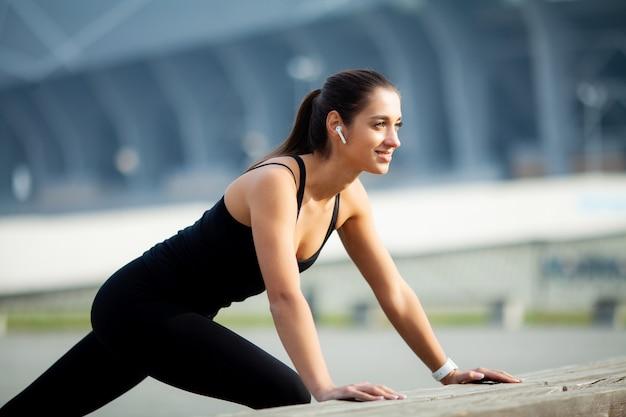 Фитнес, красивая молодая девушка с идеальными мышцами Premium Фотографии