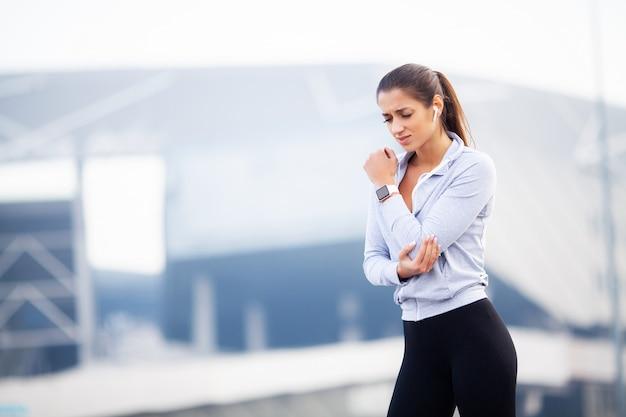 フィットネス、女性は、屋外、筋肉痛の概念でのトレーニング中に事故で負傷し、腕を傷つける Premium写真