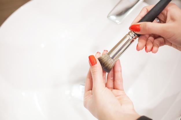Щетка для макияжа, женщина моет грязную кисточку для макияжа с мылом и пеной в раковине Premium Фотографии