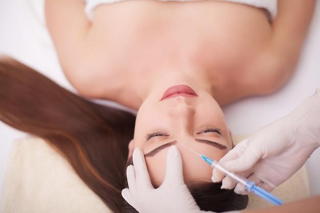 Руки косметолога делают инъекции в лицо, губы. молодая женщина получает инъекции красоты лица в салоне. процедуры старения лица, омоложения и увлажнения. эстетическая косметология. закройте Premium Фотографии