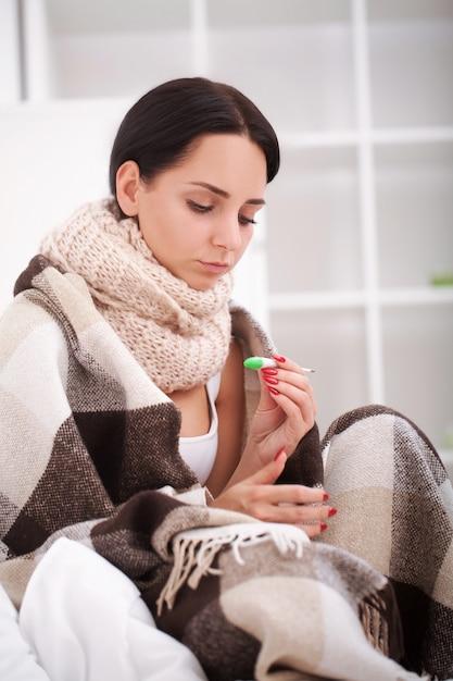 Грипп. молодая женщина с простудой, лежа на кровати Premium Фотографии