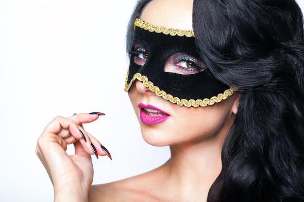 ヴェネツィアマスクスタジオポートレートを持つ魅力的な若い女性。 Premium写真