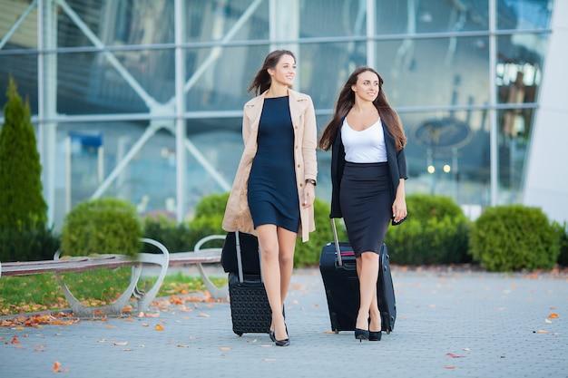 Отпуск, две стильные женщины-путешественники гуляют с багажом в аэропорту Premium Фотографии