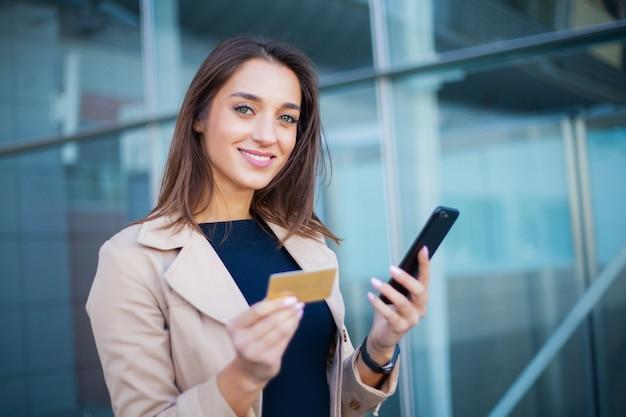 Низкий угол довольной девушки, стоящей в зале аэропорта, он использует золотую кредитную карту и мобильный телефон для оплаты Premium Фотографии