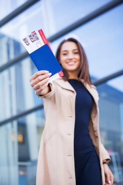Путешествие, женщина держит два авиабилета в заграничном паспорте возле аэропорта Premium Фотографии