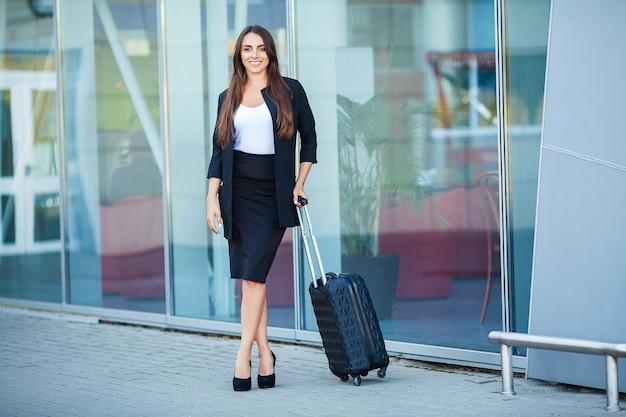Путешествие, молодая женщина идет в аэропорту у окна с чемоданом в ожидании самолета Premium Фотографии
