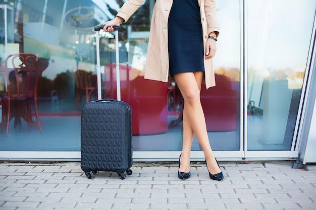 屋外の都市の道路でスーツケースと夏のカジュアルな服で足を組んで画像旅行者観光女性をトリミング Premium写真