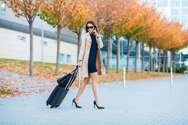 旅行、ゲートに行く空港で手荷物を持って歩きながらスマートフォンで話している空港のビジネスウーマン、会話に携帯電話を使用して女の子 Premium写真