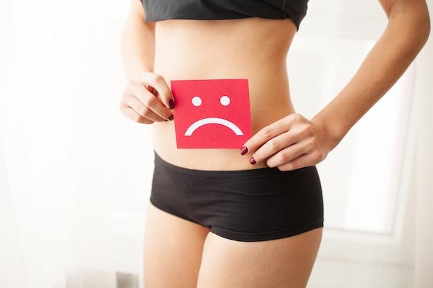 Вагинальные или мочевые инфекции и проблемы концепции. молодая женщина держит бумагу с грустной улыбкой выше промежности Premium Фотографии