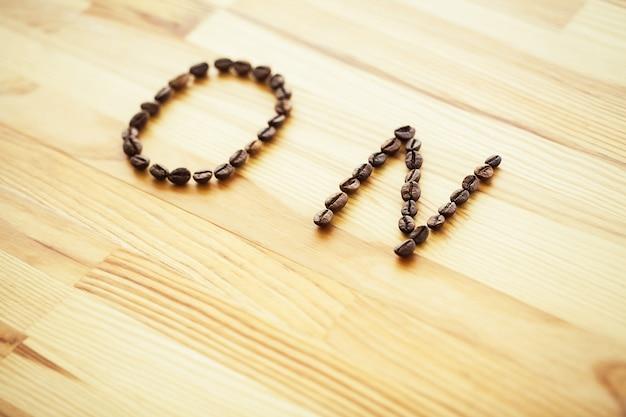 おはようございます。コーヒータイム。コーヒーと木製のテーブルの豆 Premium写真