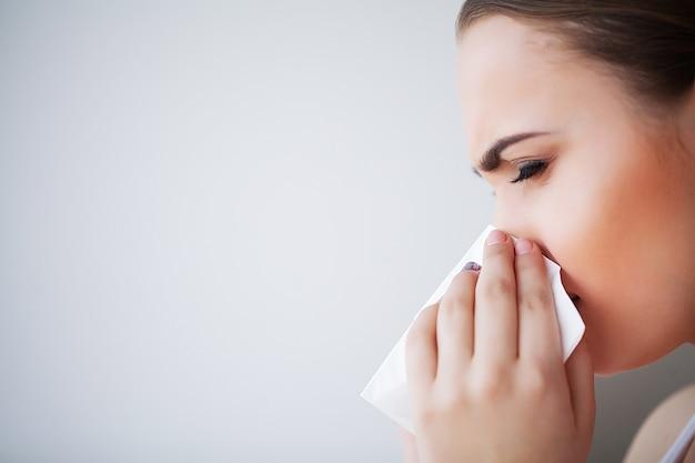 インフルエンザと病気の女性。ペーパーティッシュ、頭の冷たい問題を使用して病気の女性 Premium写真