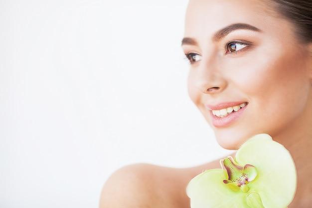 スキンケア。完璧な肌と彼女の顔の近くの蘭の花と美しいモデルの女性 Premium写真