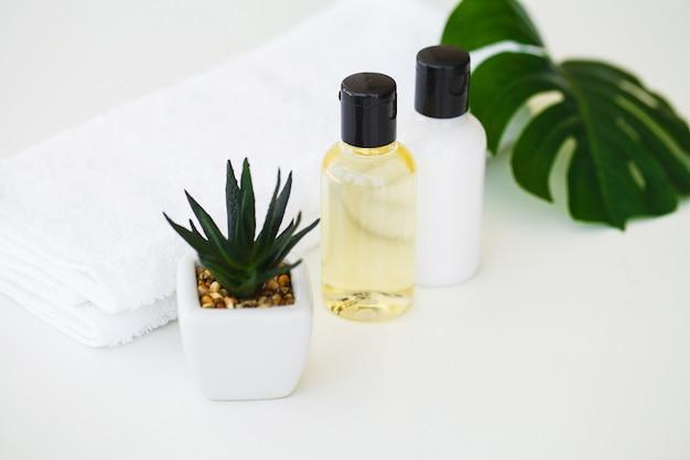 ウェルネス製品と化粧品。バラの花とエッセンシャルオイルのあるスパ静物 Premium写真