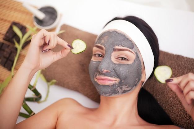 ビューティーサロン、ウェルネスの女性。目のマスクの緩和とキュウリのスライスの化粧品の手順女性の顔 Premium写真