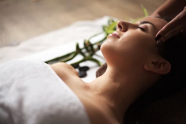 ビューティーサロンで顔の治療を得る美しい若い女性。 Premium写真