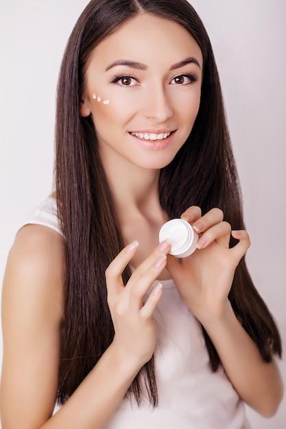 美容スキンケア。きれいな顔に化粧品クリームを適用する美しい幸せな女。 Premium写真