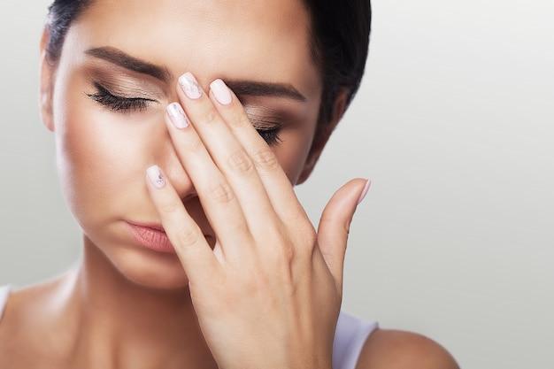 目の痛み強い目の痛みに苦しんでいる美しい不幸な女性。悲しい女性の気持ちのストレスのクローズアップの肖像画。 Premium写真