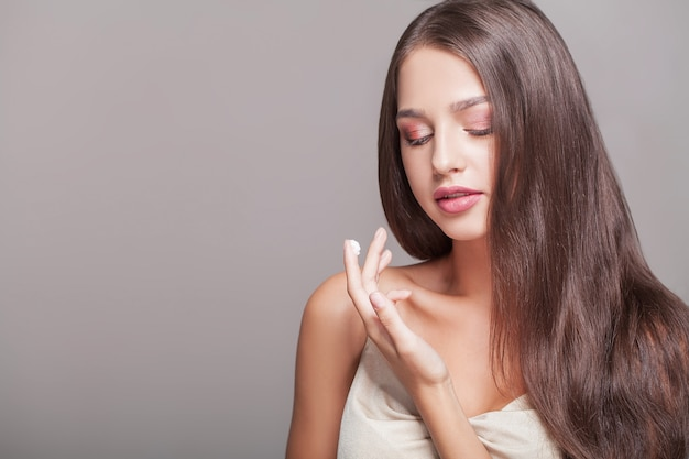 スキンケア 。ハンドクリーム、彼女の手にローションと美しい女性。 Premium写真