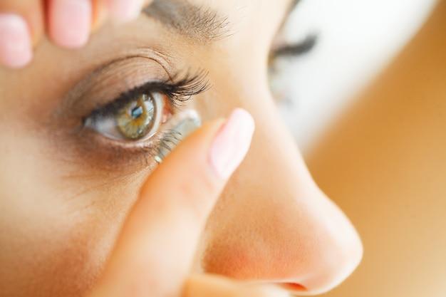 目の目のレンズを適用する美しい女性のクローズアップ Premium写真