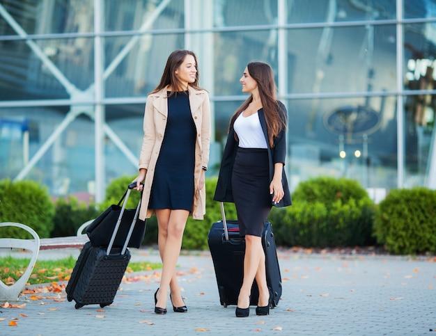 Отпуск. две счастливые девушки путешествуют вместе за границей с чемоданом в аэропорту Premium Фотографии