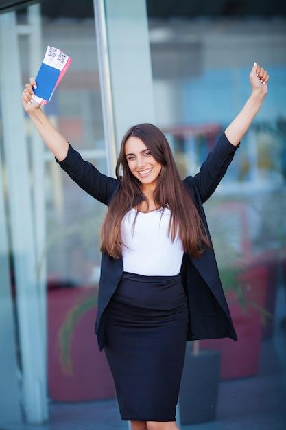 Путешествовать. женщина держит два авиабилета в заграничном паспорте возле аэропорта Premium Фотографии
