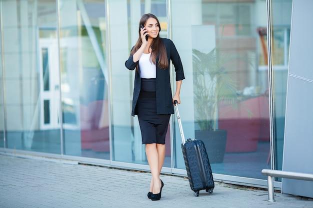 旅行。若い女性は飛行機を待っているスーツケースとウィンドウで空港に行きます Premium写真