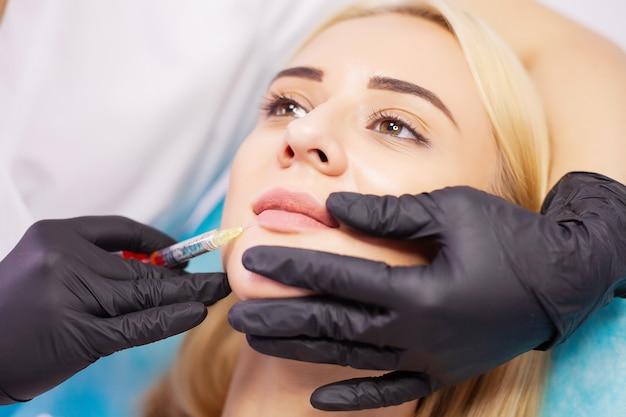 美容クリニックでの唇の拡張。美しい女性の唇の美容注射を取得します。 Premium写真