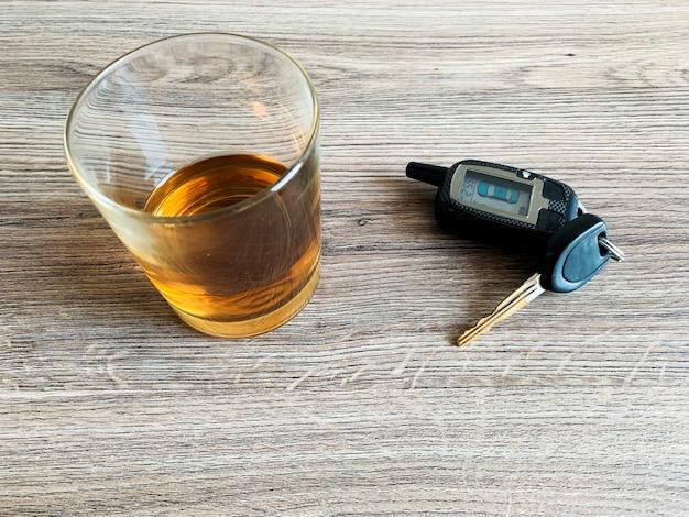 飲酒運転のコンセプト。テーブルの上のウイスキーと車のキーとガラス。 Premium写真