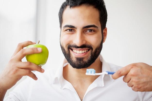 リンゴを食べる男。リンゴをかむ白い歯を持つ美しい少女。 Premium写真