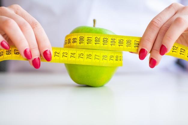 ダイエット。フィットネスと健康食品のダイエットコンセプト。野菜とバランスの取れた食事。青リンゴを測定陽気な医師栄養士の肖像画。自然食品と健康的なライフスタイルのコンセプト。 Premium写真