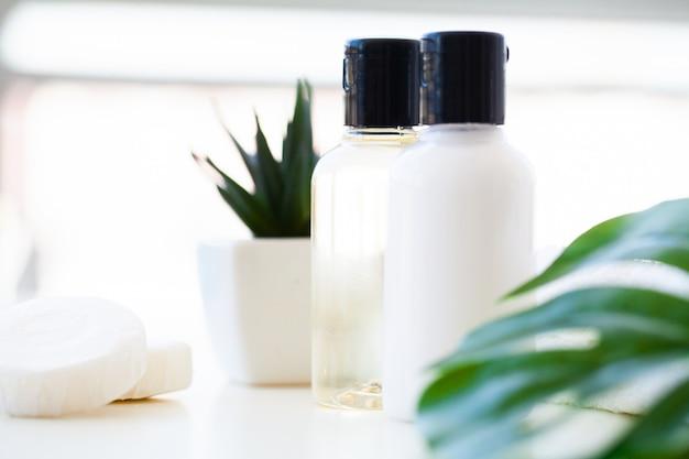 ウェルネス製品と化粧品。ハーブとミネラルのスキンケア。クリーム色の瓶、白い化粧品ボトル。ラベルなし。石鹸と白いタオルのスパセット。 Premium写真