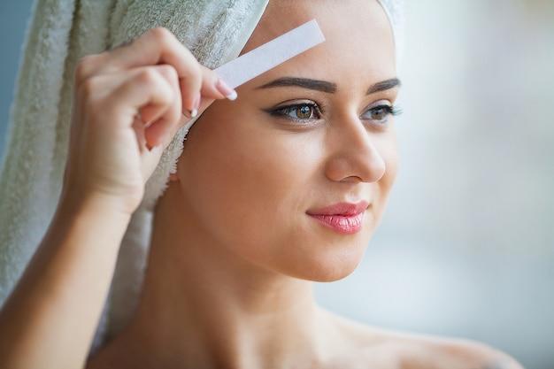 スパセンターで若い女性の眉毛をワックス美容師 Premium写真