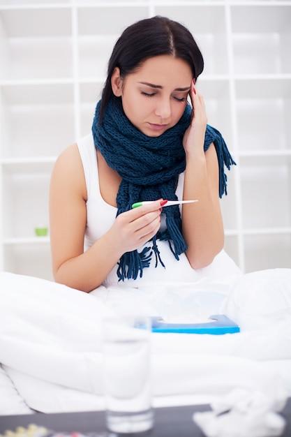 Больная молодая женщина кашляет на кровати Premium Фотографии