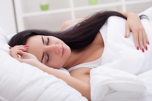 寝室のベッドで寝ている美しい若い女性 Premium写真
