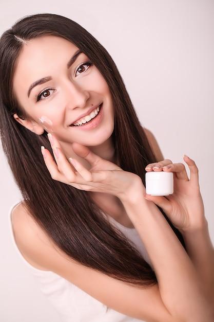 清潔でさわやかな肌を持つ美しい若い女性は、顔に触れます。フェイシャルトリートメント、美容、美容、スパ Premium写真