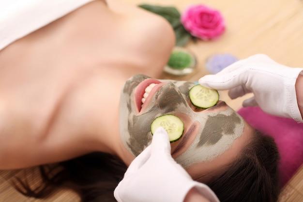 美容健康スパセンターで横になっている顔のマスクを持つ少女 Premium写真