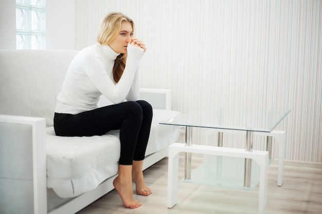 Молодая женщина чувствует себя в депрессии дома Premium Фотографии
