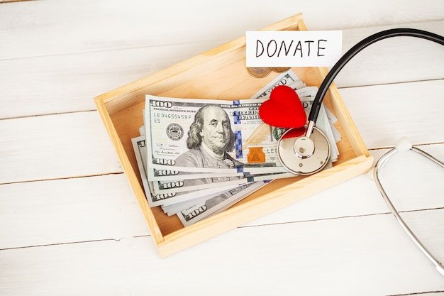 寄付と慈善。寄付。寄付の箱と白の心。 Premium写真