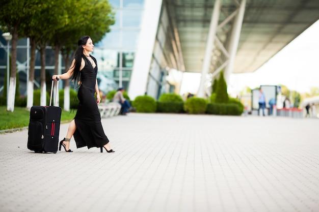 スーツケースを持つ若い陽気な女性。旅行と仕事の Premium写真