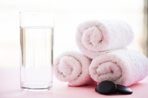 スパ。ピンクのスパバスルームで白い綿タオルを使用 Premium写真