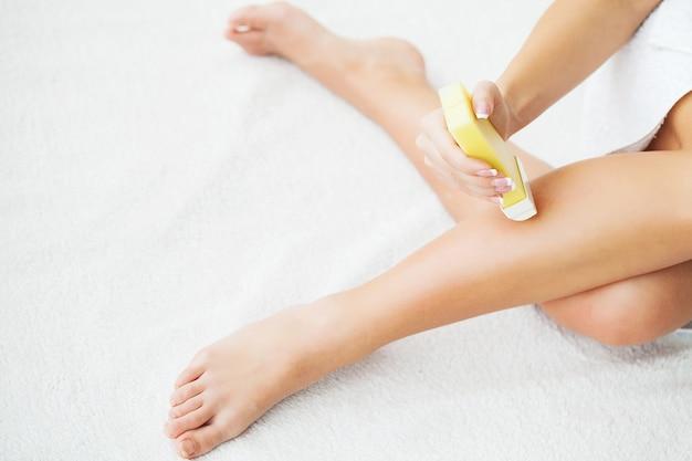 ポータブルロールオン脱毛器で足をワックスする女性 Premium写真